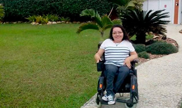 Foto horizontal de uma jovem sorrindo em uma cadeira de rodas, de calça jeans, blusa branca listrada, óculos. Do lado esquerdo, um grande jardim.