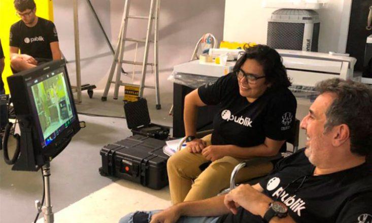 Um homem e uma mulher assistem uma filmagem em um computador, em um estúdio de gravação. Ambos estão sentados, vestindo uma blusa preta com a logo Publik no peito, em letras brancas. Do lado esquerdo, ao fundo, um jovem com a mesma camiseta, observa algo no chão.