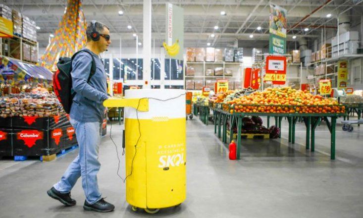 Homem cego conduz o carrinho acessível da SKOL em um supermercado. O equipamento tem formato semelhante ao de uma lata de cerveja, está pintado de amarelo e branco, e tem a logomarca do produto.