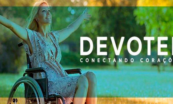Imagem de uma cadeirante de braços abertos, em um grande jardim. Ao centro, uma faixa esverdeada sobre a foto original e as palavras, em branco: DEVOTEE Conectando Corações