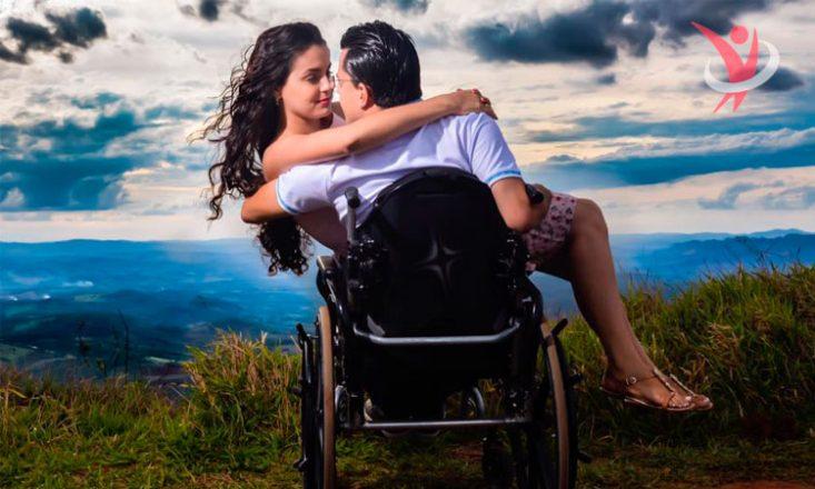 Casal de namorados em à beira de um precipício e, ao fundo, o oceano embaixo e as nuvens no céu. O homem está de costas sentado em uma cadeira de rodas e a mulher está em seu colo. Estão abraçados e olhando um para o outro. No canto superior direito, a logomarca do blog Sem Barreiras em vermelho e em marca d'água.
