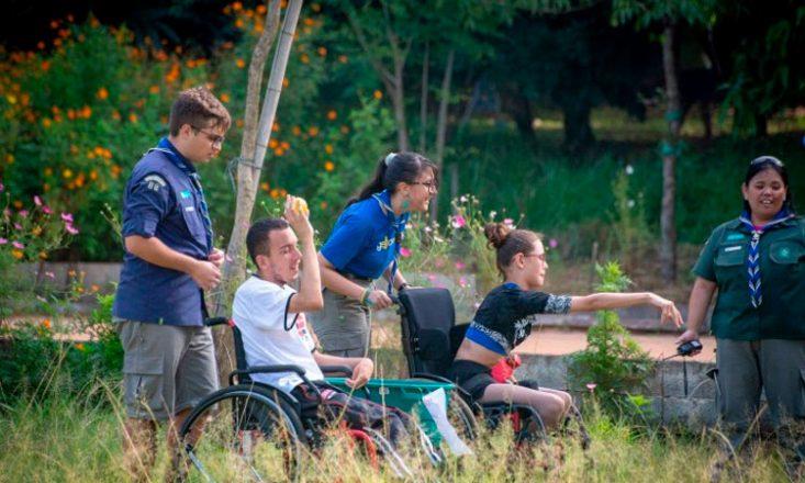 Duas pessoas em uma cadeira de rodas, um homem em primeiro plano e uma jovem mais ao fundo, junto com três instrutores participando de uma atividade de escotismo em um parque