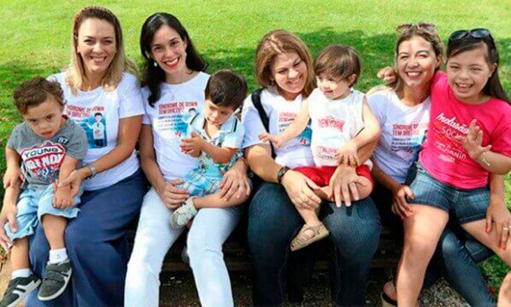 Quatro mulheres sentadas na grama, no que parece ser um parque, com quatro crianças com deficiência em seus colos.