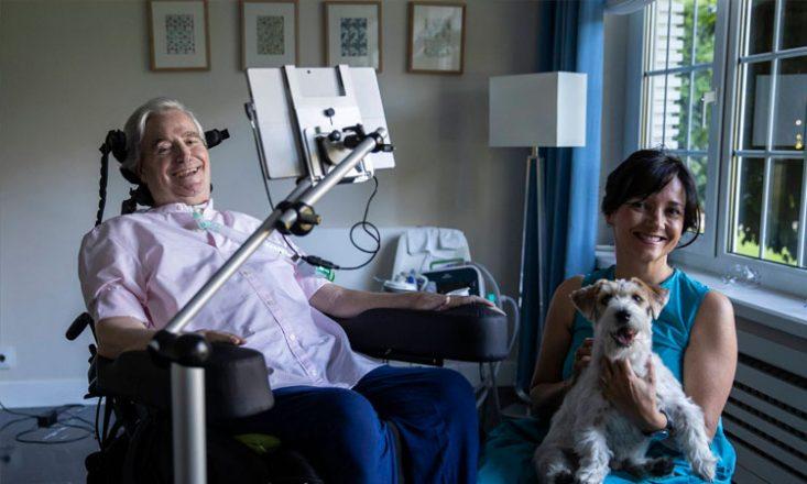 Homem na sala de sua casa, em uma cadeira de rodas, com uma tela na frente do seu rosto, presa a um braço mecânico conectado à cadeira. Ao seu lado, sentada em um banco, uma mulher sorri e segura um cachorrinho no colo.