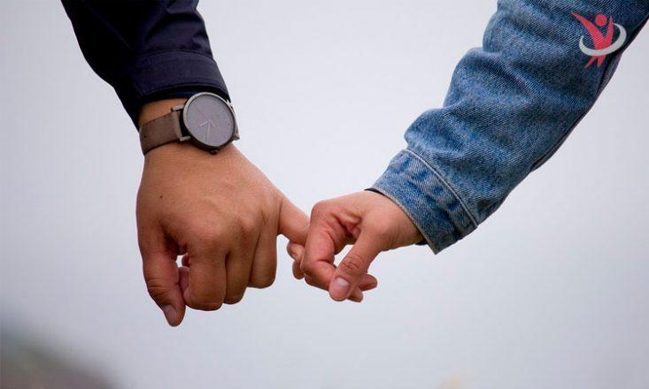 Foto de dois braços saindo do alto da imagem. À esquerda, o braço esquerdo de um homem, com o dedo mínimo entre os dedos da mão feminina ao seu lado. No canto superior direito, a logomarca de Sem Barreiras, em vermelho e marca d'água.