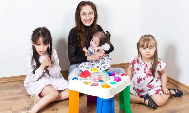 Uma mulher ao centro, com uma garotinha autista no colo, uma outra cega à esquerda e uma terceira, com Síndrome de Down, à direita. À frente, uma mesinha de brinquedo.