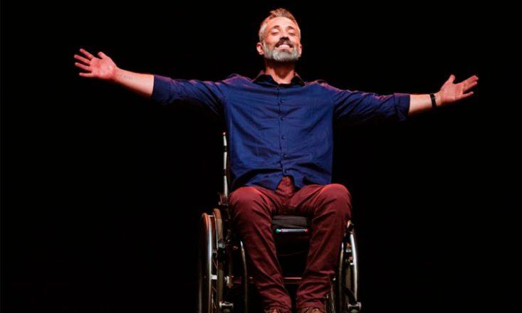 Homem em uma cadeira de rodas, de braços abertos, olhos fechados e sorrindo. Ao fundo, uma tela preta.