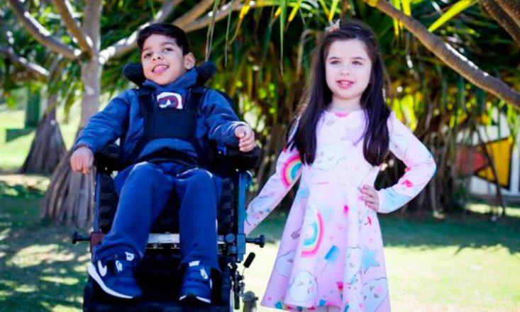 Vitor, em sua cadeira de rodas, e Allice posam juntos, lado a lado, em um parque com grama e muitas árvores ao fundo.