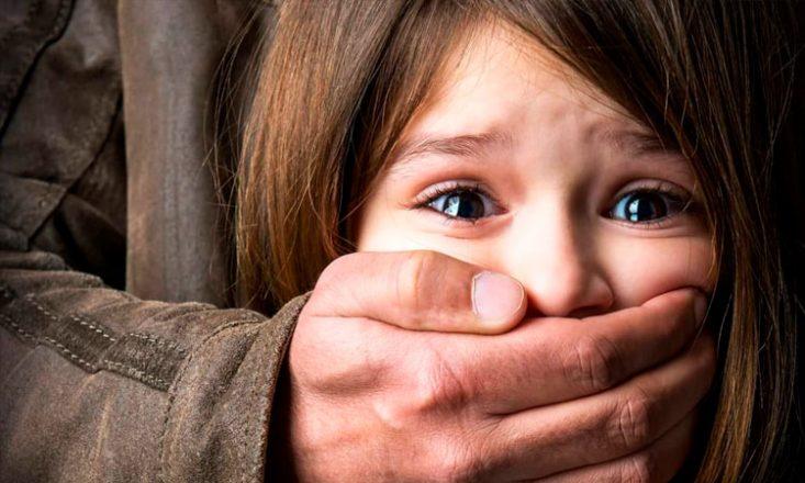 Menina com os olhos arregalados tem a boca tampada pela mão de um homem atrás dela.
