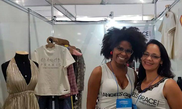Duas mulheres, lado a lado, sorrindo, no canto inferior direito da imagem. À esquerda, algumas roupas penduradas em cabides.
