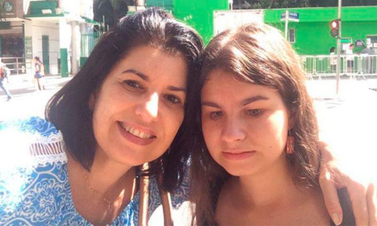 Mãe e filha abraçadas, lado a lado, no que parece ser uma instituição de ensino. A mãe, à esquerda, sorri, e a filha deficiente visual, tem os olhos voltados para baixo.