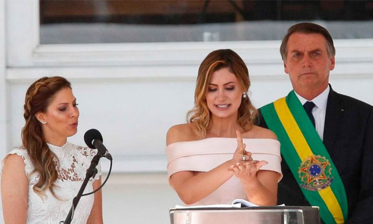 Três pessoas, lado a lado. Ao centro, a primeira-dama Michele Bolsonaro faz discurso em Libras. Do lado esquerdo, a intérprete oficial do governo e, à direita, o presidente Jair Bolsonaro.