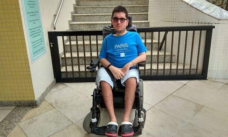 Rapaz, ao centro da foto, sentado em uma cadeira de rodas. Atrás dele, uma grade e uma escadaria.