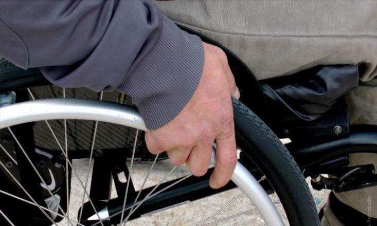 Imagem lateral de um homem em uma cadeira de rodas, mostrando somente sua mão direita segurando a roda.