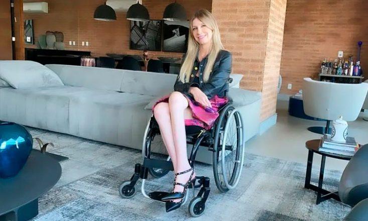 Foto de Andrea Schwarz, mulher branca, com cabelos loiros, lisos e compridos. Está sentada em uma cadeira de rodas, com as pernas e os braços cruzados, com as mãos sobre as coxas. Sorri e olha para a câmera. Veste jaqueta de couro escura sobre uma blusa preta e saia com tons de rosa. Calça sapatos finos de salto agulha. Ao redor, móveis e objetos de decoração em uma sala de estar com paredes de tijolos vermelhos e chão cinza.