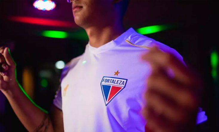 Modelo deficiente visual posa com o uniforme Fortaleza Glória 1970, uma camisa branca, com o escudo do time no lado esquerdo, uma linha dourado no ombro e a logo do fabricante, também dourado, do lado direito. Ao fundo, luzes verdes e vermelhas.