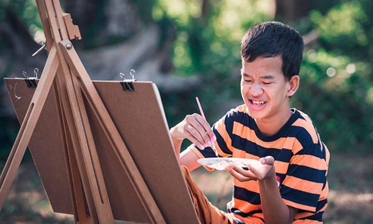 Adolescente com deficiência intelectual, vestindo uma camiseta listrada em preto e laranja, segura um pincel e um prato de tintas, defronte a uma tela e um cavalete. Ao fundo, árvores e plantas.