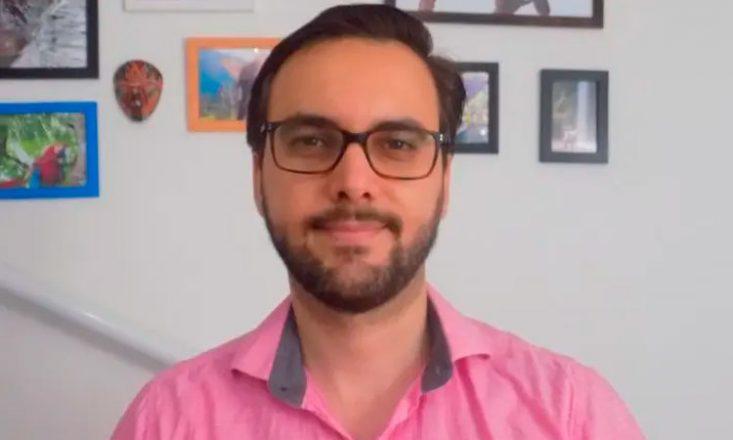 Foto de Victor Martinez, homem branco, com cabelos pretos, curtos e penteados para trás, barba escura e óculos de aros retangulares e pretos. Veste uma camisa rosa. Olha para a câmera, com um leve sorriso. Ao fundo, uma parede com quadros e fotografias.
